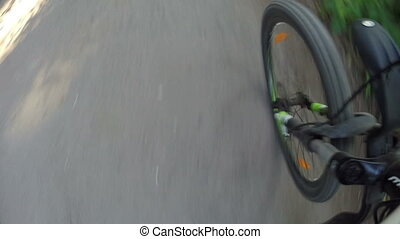 Top view of the road: the bicycle wheel rotates rapidly and...