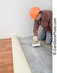flooring installation - Construction worker gluing linoleum