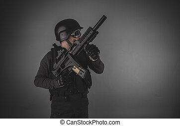 aiming, airsoft player with gun, helmet and bulletproof vest...
