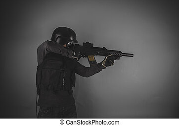 airsoft player with gun, helmet and bulletproof vest on gray...