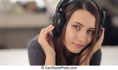 Woman Enjoys Listening to Music on the Bed
