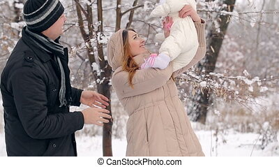 Happy Young Family in Winter - Young Happy Family with baby