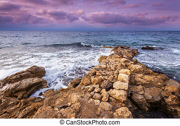 Sea waves with rocks on the beach at sunset