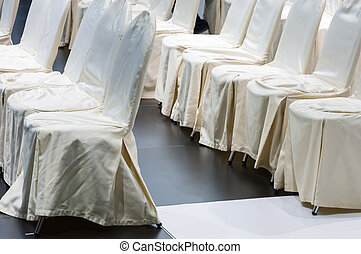 Row of white chair in the small presentaion event.