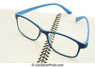 eyeglasses on a blank paper notepad - eyeglasses on a blank...