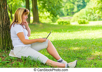 Happy mature woman in the park with a laptop