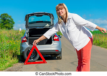 emergency stop - female 50 years, sets on the road warning...