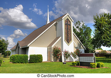 Beautiful christian church with white steeple cross and blue sky