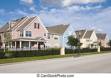 Colored homes - Colorful fenced in row houses with blue sky