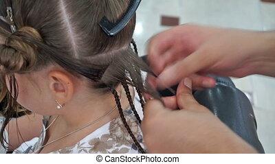 Hairdresser hands weaving a dreadlocks for girl -...