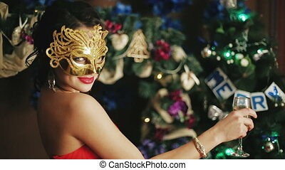 Beautiful sexy lady in the mask drinking champagne
