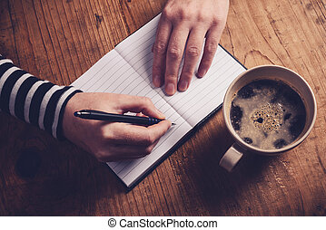 Woman drinking coffee and writing a diary note - Woman...