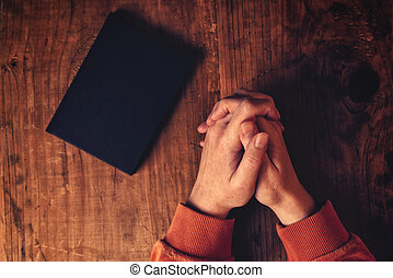 Hands of Christian woman praying with Holy Bible by her side...