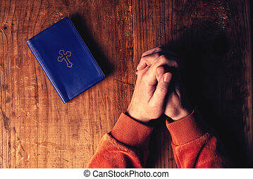 Christian woman praying with hands crossed and Holy Bible by...