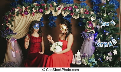 Two beautiful lady in Venetian masks drinking champagne