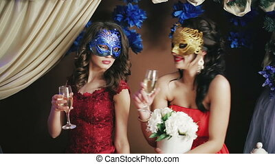 Two beautiful lady in Venetian masks drinking champagne....
