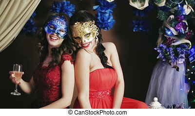 Two beautiful lady in Venetian masks drinking champagne. Close-up