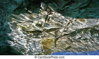 Glare of sun from water on walls of cave in marble quarry in...