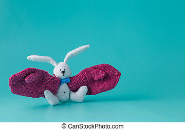Funny white bunny with big mittens on aquamarine background