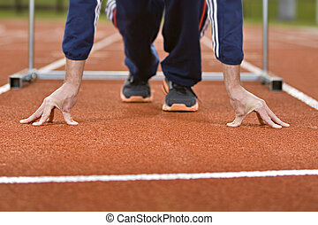 Hurdle Athlete - Athlete in sprint position on a running...