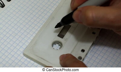 Audio Cassette Labeling Demo - Close up handheld shot of a...