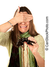 Woman covering her eyes after using binoculars - Adult woman...