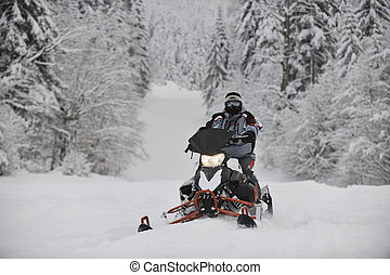 snowmobile - young man posing on snowmobile at beautiful...