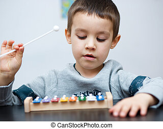 Boy is playing a musical instrument