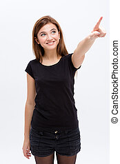Cheerful lovely cute young woman looking and pointing away
