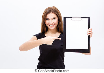 Cheerful attractive young woman showing clipboard and...