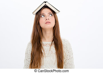 Thoughtful amusing young woman with book on her head
