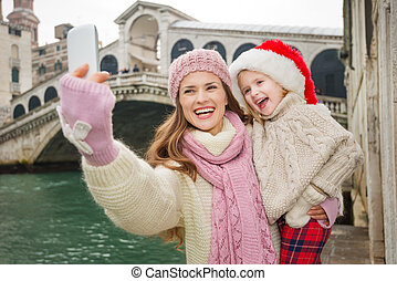 Happy mother and child in Santa Hat taking selfie in Venice...