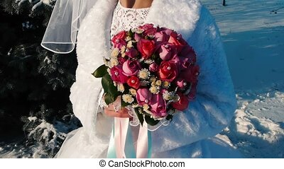 Bride holds a wedding bouquet in her hands Outdoors.