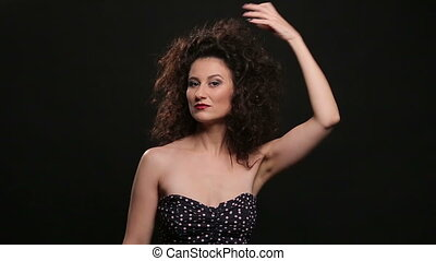 Young brunette with long brown curly hair dancing