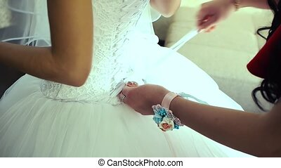 Bridesmaid is lacing white wedding dress for beautiful...