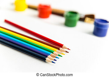 Colorful pencils for drawing lying near gouache paints and...