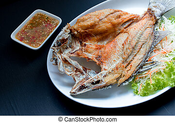 Fish dish - Deep fried Snapper fish eat with spicy sauce on black background