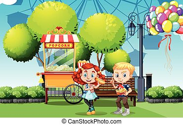 Boy and girl eating in the park