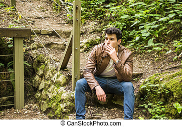 Young man sitting and smoking in park - Handsome young man...
