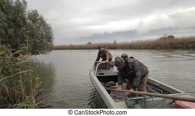 Looking fishing spots - Fishermen travel by motorboat along...