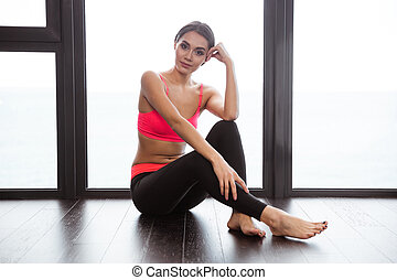 Sports woman sitting on the floor in fitness gym - Portrait...