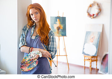 Thoughtful atractive young woman painter holding art palette...