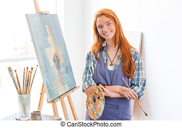 Happy satisfied woman painter finished painting picture in...
