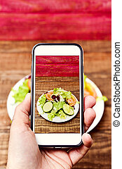 man taking a picture of a salad with his smartphone -...