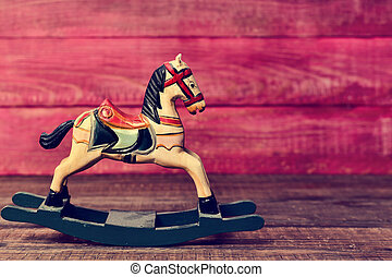 old toy horse on a wooden surface - an old wooden rocking...