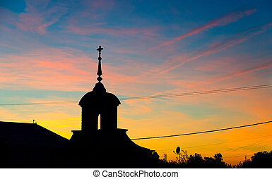 Silhouette of church against the colorful sunset