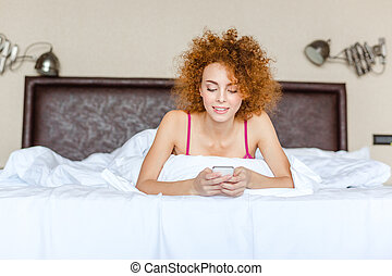 Cute lovely curly woman using mobile phone lying in bed -...