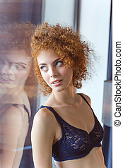Alluring tender woman in lace bra standing at the window -...