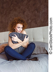 Playful beautiful young woman hugging cushion on bed in bedroom