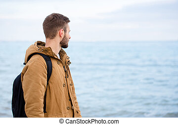 Man looking at the sea outdoors - Portrait of a casual young...